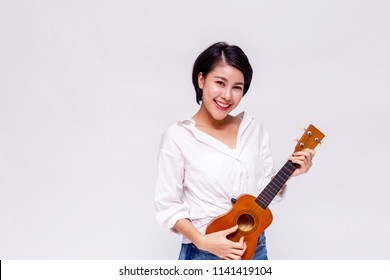 Young Asian female girl playing ukulele beach guitar in white isolated background