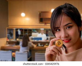 Young Asian female hold golden bitcoin coin in hand with blurred background of Japanese restuarant in concept of using Bitcoin as money for food payment