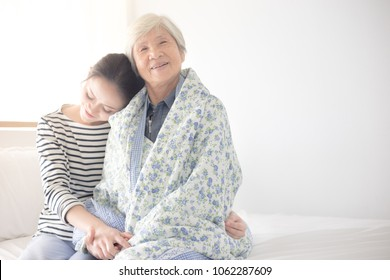 young Asian female hug old female, mother's day , family time, hand in hand