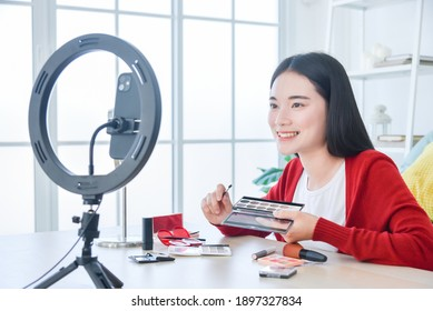 Young Asian female makeup artist , beauty vlogger or blogger recording  cosmetic makeup tutorial vlog by smart phone ,share on social media live streaming Internet.