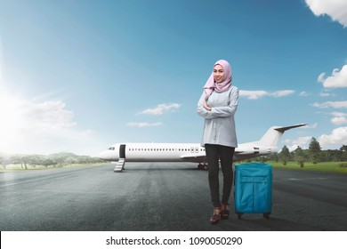 Young asian female muslim with suitcase going traveling by airplane