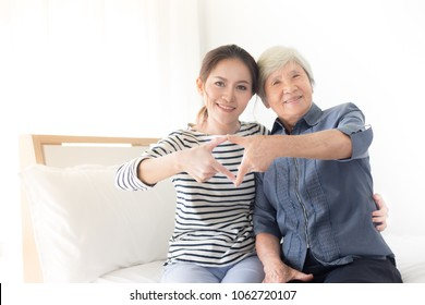 young Asian female and old Asian female show heart sign with hand, mother's day , family time