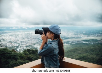 Young asian female photographer with camera outdoors at the park. Thai woman holding camera in hand.