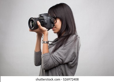 Young asian female photographing with SLR on an isolated background.