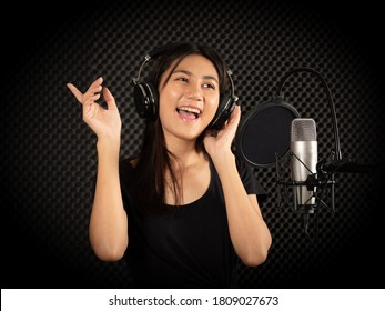 Young Asian female professional singer singing in front of microphone, recording the songs in the studio.