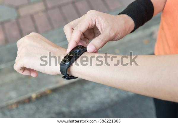 Joven corredor asiático que pone en el monitor de pulsera la banda de reloj inteligente dispositivo portátil listo para hacer ejercicio por la mañana para un deporte saludable hacer ejercicio verano primavera día soleado