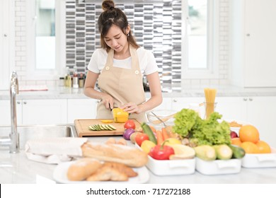 Young asian female slicing paprika on cutting board at the kitchen, prepare the ingredient for cooking salad for her family