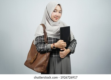 Young Asian female student standing with grey background