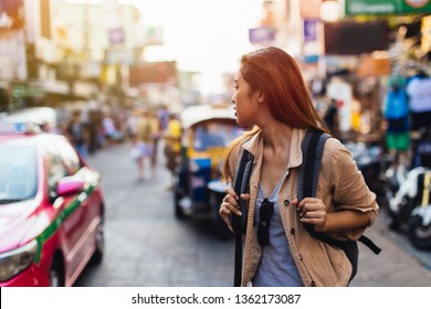 Young Asian female tourist woman walking and backpacking on Khaosan road in Bangkok, Thailand. Travel and Backpack in Asia concept