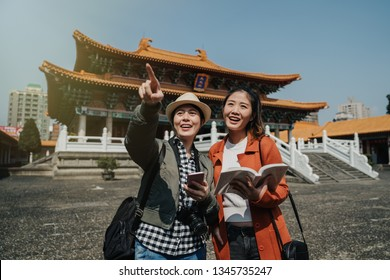 Young asian female tourists holding guide book cellphone stand in travel destination in bangkok thailand. japanese woman travelers summer trip in china beijing visit temple. happy girl point finger