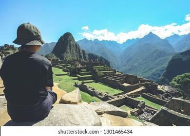 A young asian female traveler is admiring the Inca ruins of Machu Picchu, one of the New Seven Wonder of The World, Cusco Region, Urubamba Province, Peru.