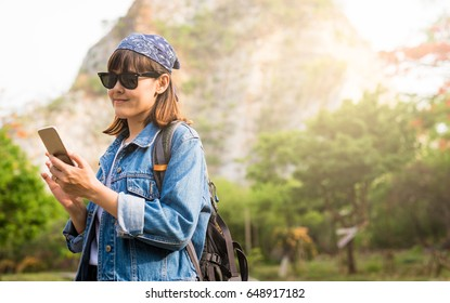 Young asian female traveler backpack using smartphone on mountain background.