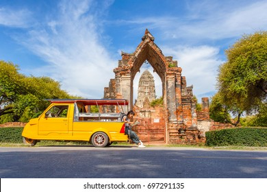 Young asian female traveler with backpack traveling sitting on taxi or Tuk Tuk and see map travel with old temple (Wat Mahathat) background, Ayutthaya Province, Thailand