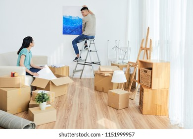 Young Asian female unpacking boxes and looking at boyfriend hanging painting on wall while moving into new apartment