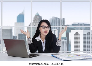 Young asian female worker doing her job in the office and looks confused