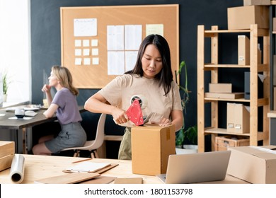 Young Asian female worker of online shop office or store-room packing one of cardboard boxes with order while sealing it with cellotape