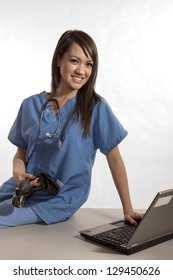 Young asian filipino nurse working on laptop
