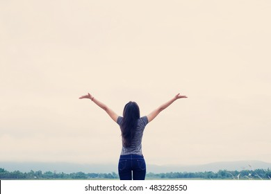 Young Asian fit woman relaxing with the river nature. Happy time morning. open arms up to the sky.