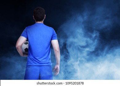 Young asian footballer with the ball on abstract background