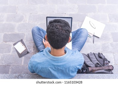 Young Asian freelancer guy in headphones sitting on floor and working on laptop