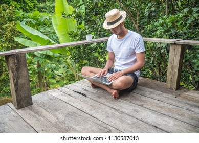 Young Asian freelancer guy using laptop computer while is sitting against jungle scenery during vacation holiday in summer journey