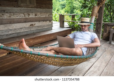 Young Asian freelancer guy using laptop computer while is sitting and relaxing on hammock during vacation holiday in summer journey