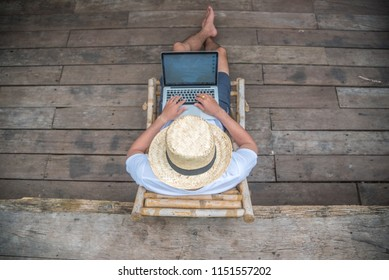 Young Asian freelancer guy using laptop computer while is sitting against jungle scenery during vacation holiday in summer journey, top view blur background