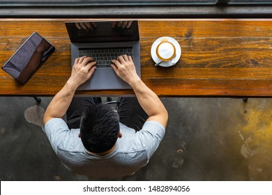 Young Asian freelancer using laptop and tablet at beautiful coffeeshop