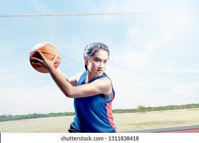 Young asian girl basketball player defending the ball from opponent on the outdoor basketball court with grassland and sky background