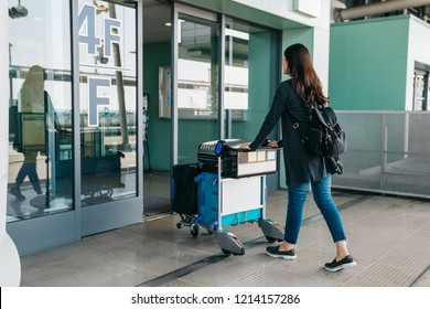 young asian girl carrying luggage entering international airport. elegant woman rolls light cart with luggage through the auto door in four floor. pretty lady going abroad to backpack travel.