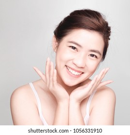 young asian girl with clean skin, Cosmetic Beauty Concept,hands touch on the cheek, smiling and friendly face isolated on grey background