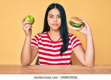 Young asian girl comparing burger and healthy apple relaxed with serious expression on face. simple and natural looking at the camera.