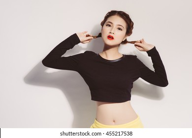 Young asian girl doing emotion. Dressed in a black shirt and yellow skirt.  Warm color. White background, not isolated