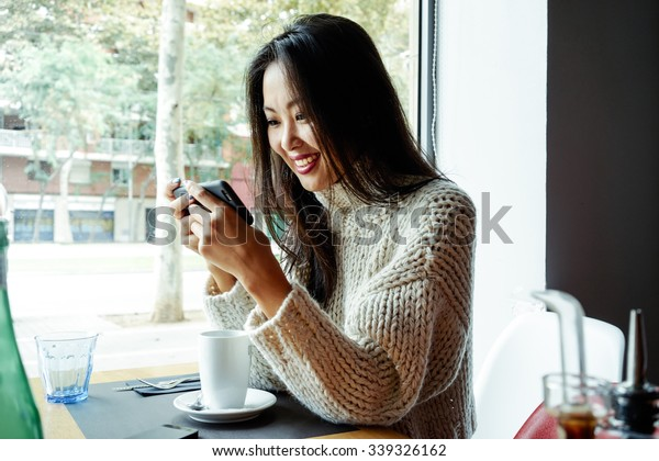 Young Asian Girl drinking coffee / tea and using digital smart-phone in a coffee shop