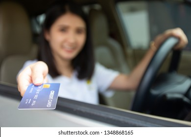 Young Asian girl driving car hand holding credit card payment for gasoline at petrol station. Happy woman car owner paying fuel pump with credit card, customer mileage point loyalty reward concept.