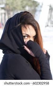 young Asian girl with dyed hair hides her face in a hood