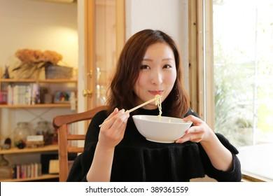 Young Asian girl eating ramen noodles using chopsticks.