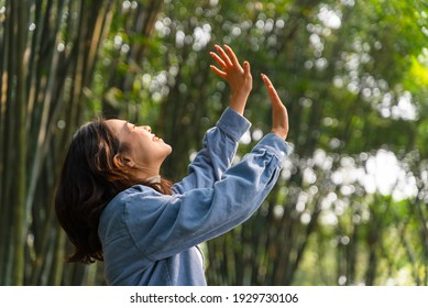 Young Asian girl enjoying beautiful spring in sunny bamboo forest