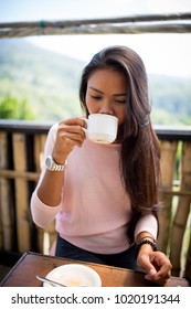 Young Asian girl enjoying a coffee.