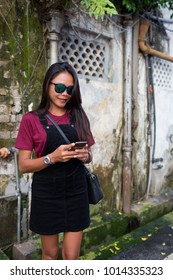 Young Asian girl enjoying the day in the old section of the city while using her phone.