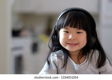 A young asian girl enjoying listening to music on her headphone and smiling