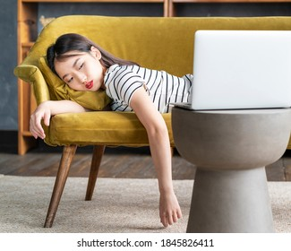 Young Asian girl fell asleep oncouch in front oflaptop. Cute bored woman watching boring movie, sad Sunday, dull leisure tired or overworked. Cozy home environment, soft sofa