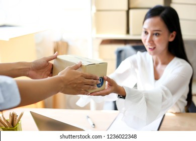 Young asian girl is freelancer Start up small business owner writing address on cardboard box at workplace,Shipping shopping online small business entrepreneur SME or freelance