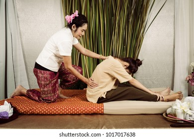 Young Asian girl get Thai style massage by Woman for body therapy