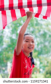young Asian girl happily grabbing Malaysia flag with background of blurred trees