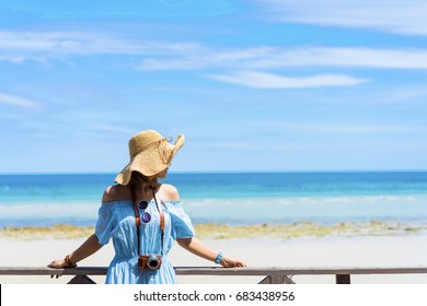 Young asian girl in hawaii dress with hat, camera on the sea beach summer lifestyle having fun and happy rest relax or leisure travel tropical in vacation time holiday bright sky.