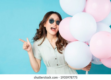 Young Asian girl holding balloons with happy expression on background