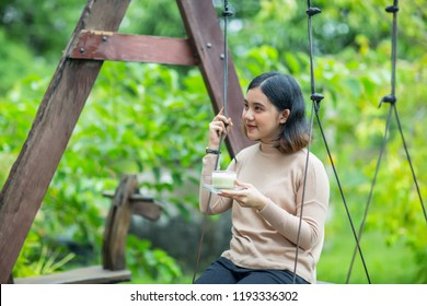 Young asian girl  holding a cup of green tea on wooden swing in the garden