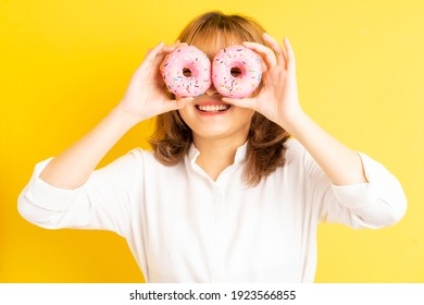 Young asian girl holding donut with cheerful expression on background