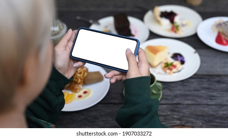 Young Asian girl holding horizontal smart phone taking photo of sweet desserts at cafe.